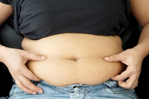 obese woman wears jeans and black t- shirt, holds her big belly by two hands-img-blog